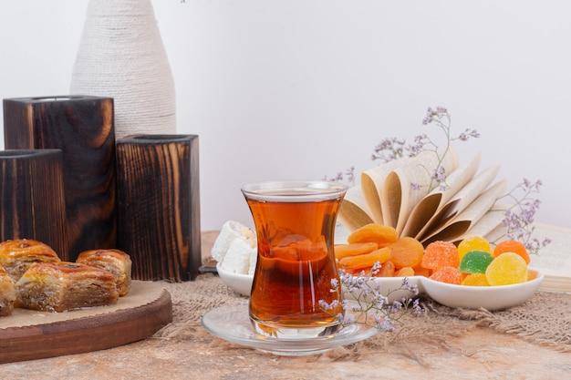 Bicchiere di tè, vari dolci e albicocche secche sul tavolo di marmo.