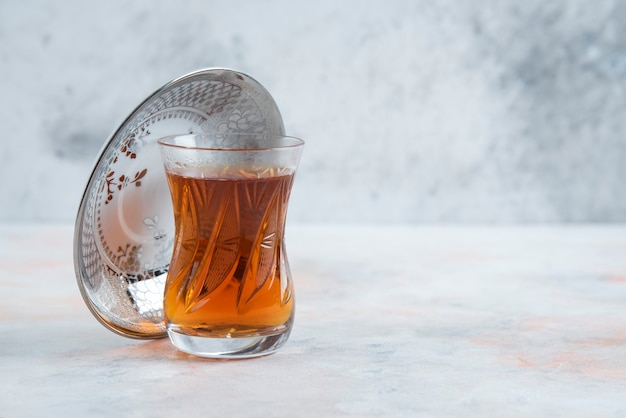 Glass of tea on white surface