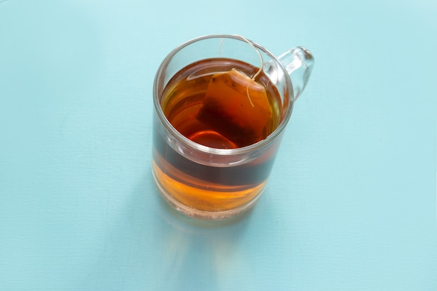 Glass of tea with a bag on a blue background