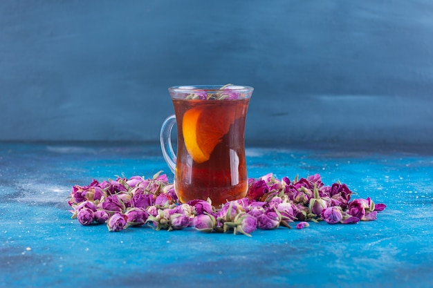 Glass of tea with budding roses placed on blue table.