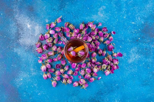 Bicchiere di tè con rose in erba poste sul tavolo blu.