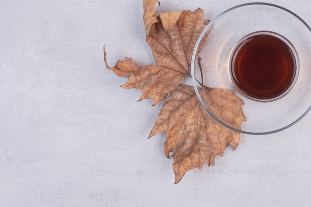 Glass of tea with dried leaves on white surface.