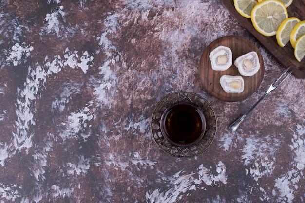 A glass of tea with lokum and sliced lemon
