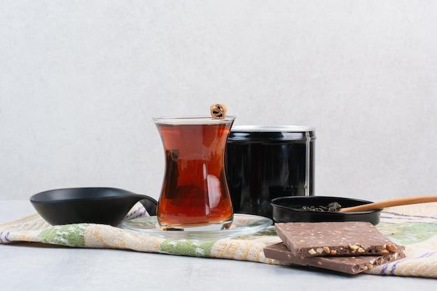 Bicchiere di tè con cioccolato alle noci sulla tovaglia