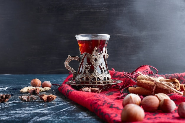 A glass of tea with nuts and cinnamons.