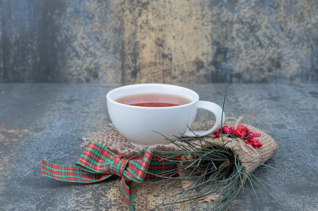 Glass of tea with ribbon and ornament on marble table. high quality photo