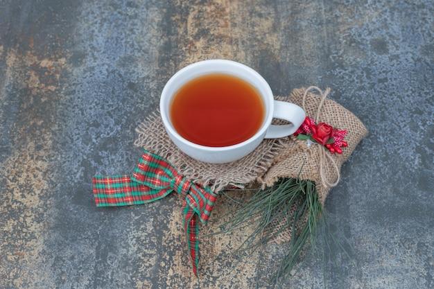 Bicchiere di tè con nastro e ornamento sul tavolo di marmo. foto di alta qualità