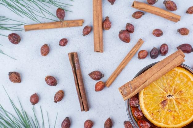 Bicchiere di tè con cinorrodi e cinnamons sulla superficie in marmo.