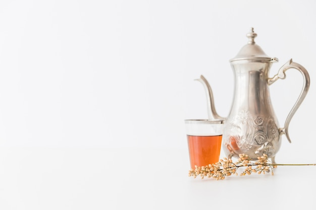 Glass of tea with teapot and branch