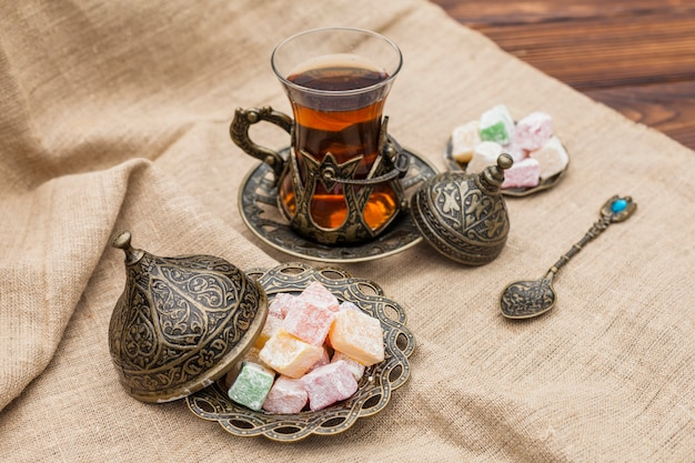 Glass of tea with turkish delight on canvas