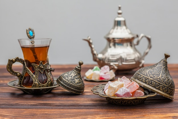Glass of tea with turkish delight and teapot