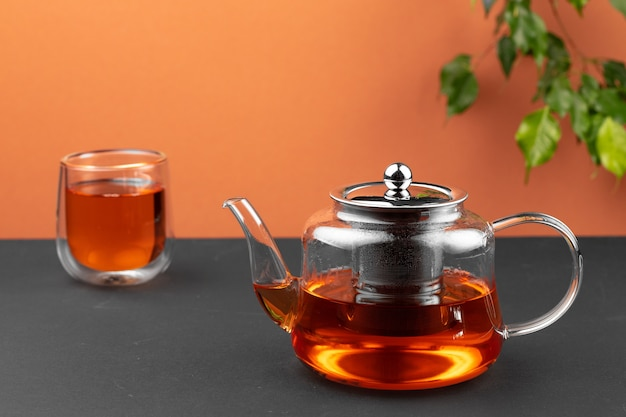 ガラスのティーポットとテーブルの上の紅茶とカップ