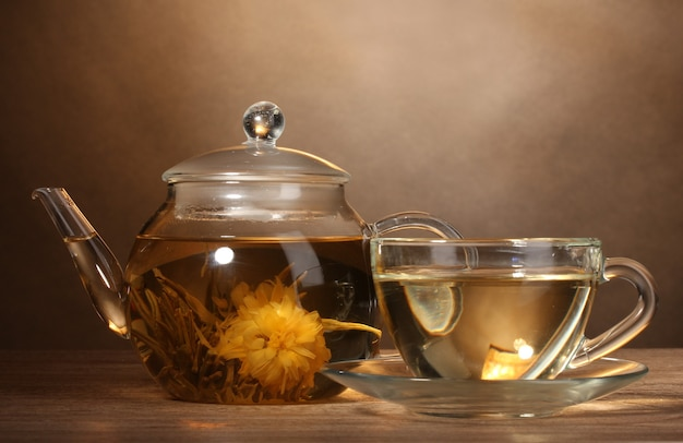 ガラスのティーポットと茶色の背景の木製テーブルにエキゾチックな緑茶とカップ