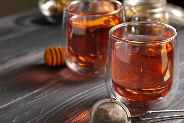 Стеклянный чайник и стеклянные чашки фруктового чая на деревянном фоне