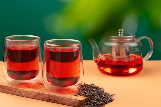 ガラスのティーポットとテーブルの上にお茶と2つのガラスのカップ