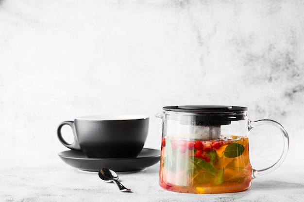 Glass teapot of cranberry, orange and mint or yellow tea on black cup isolated on bright marble background. overhead view, copy space. advertising for cafe menu. coffee shop menu. horizontal photo.