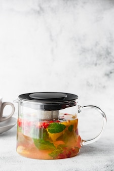 Glass teapot of cranberry, orange and mint or yellow tea with white cup isolated on bright marble background. overhead view, copy space. advertising for cafe menu. coffee shop menu. vertical photo.