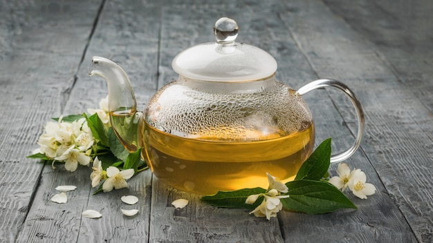 A glass teapot filled with medicinal tea with jasmine flowers. an invigorating drink that is good for your health.