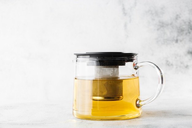 Glass teapot of green, camomile, chamomile or yellow tea isolated on bright marble background. overhead view, copy space. advertising for cafe menu. coffee shop menu. horizontal photo.