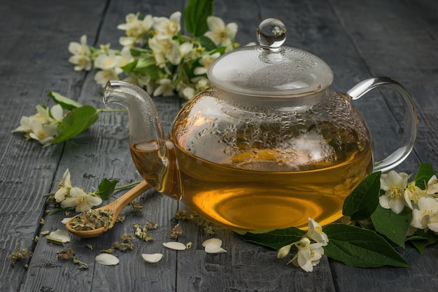 A glass teapot of jasmine tea on a black wooden table. an invigorating drink that is good for your health.