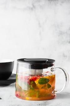 明るい大理石の背景に分離された黒いカップにクランベリー、オレンジ、ミントまたは黄色いお茶のガラスのティーポット。俯瞰、コピースペース。カフェメニューの宣伝。コーヒーショップメニュー。縦の写真。