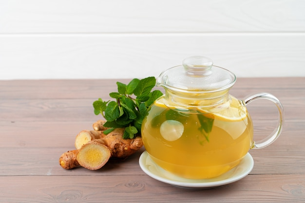 Glass teapot of tea with ginger and citrus close up
