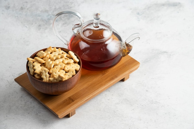 A glass teapot of tea with wooden bowl full of crackers.