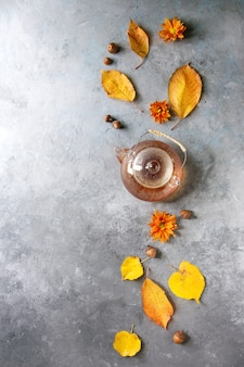 Glass teapot with autumn leaves