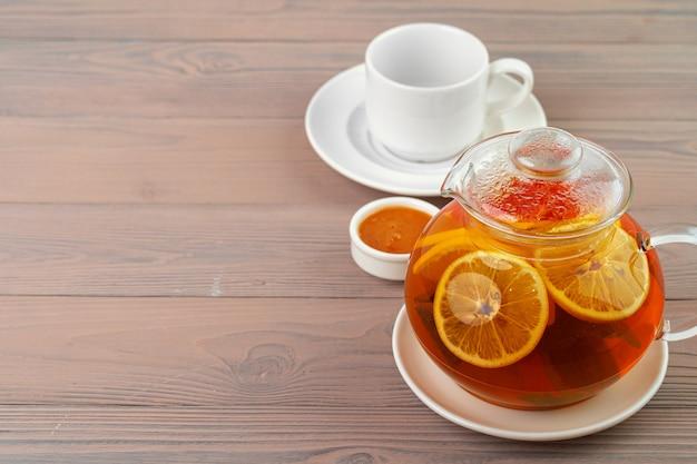 紅茶と柑橘類のかけらが入ったガラスのティーポットがクローズアップ