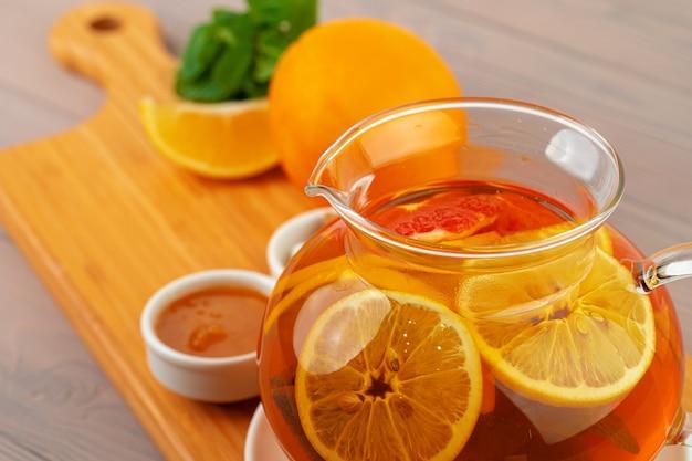 紅茶と柑橘類のかけらが入ったガラスのティーポット
