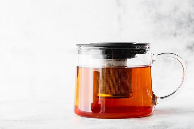 Стеклянный чайник с черным чаем, изолированные на светлом фоне мрамора. вид сверху, копирование пространства. реклама для меню кафе. меню кафе. горизонтальное фото.
