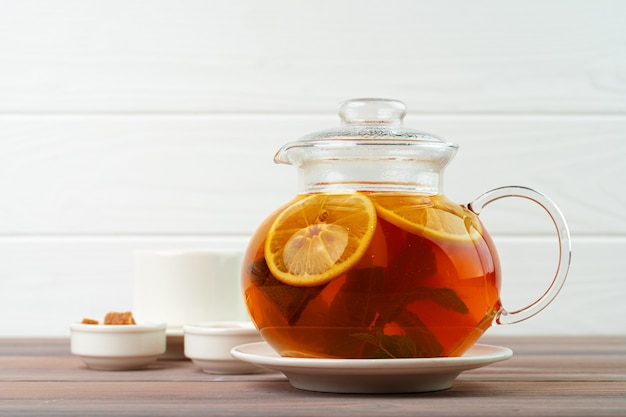 Glass teapot with black tea and pieces of citrus close up