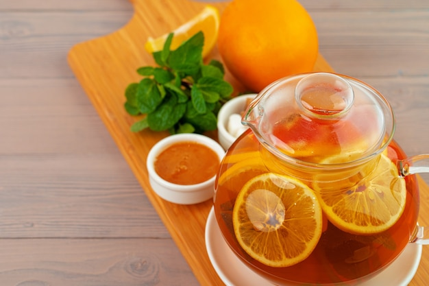Glass teapot with black tea and pieces of citrus