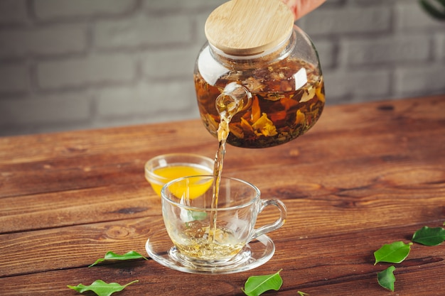 Glass teapot with cup of black tea on wooden table