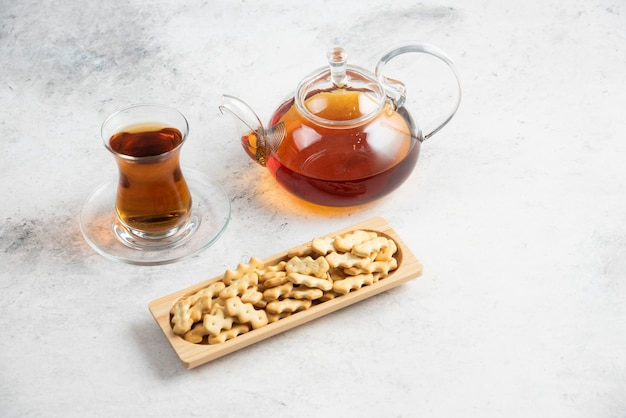 A glass teapot with a cup of tea and a wooden board full of crackers .