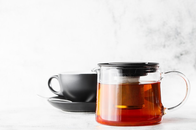 Glass teapot with dark cup of black tea isolated on bright marble background. overhead view, copy space. advertising for cafe menu. coffee shop menu. horizontal photo.