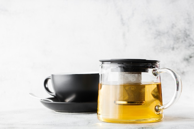 Glass teapot with dark cup of green, camomile, chamomile or yellow tea isolated on bright marble background. overhead view, copy space. advertising for cafe menu. coffee shop menu. horizontal photo.