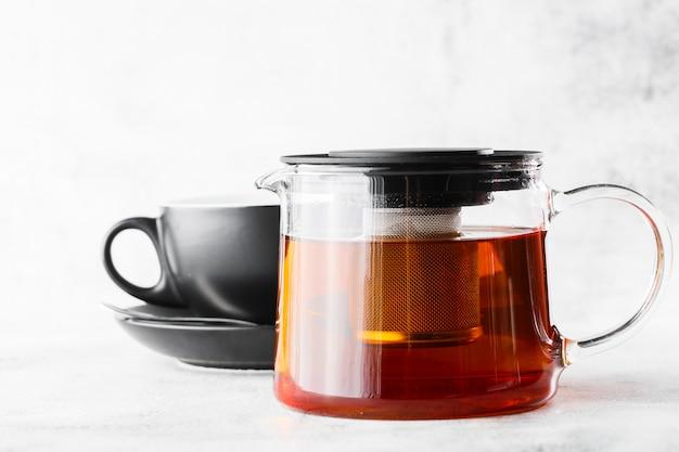 明るい大理石の背景に分離された黒茶の暗いカップとガラスのティーポット。俯瞰、コピースペース。カフェメニューの宣伝。コーヒーショップメニュー。横の写真。