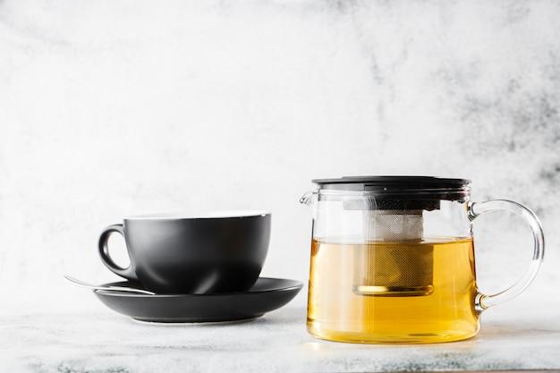 緑、カモミール、カモミールまたは明るい大理石の背景に分離された黄色いお茶の暗いカップとガラスのティーポット。俯瞰、コピースペース。カフェメニューの宣伝。コーヒーショップメニュー。横の写真。