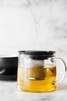 緑、カモミール、カモミールまたは明るい大理石の背景に分離された黄色いお茶の暗いカップとガラスのティーポット。俯瞰、コピースペース。カフェメニューの宣伝。コーヒーショップメニュー。縦の写真。