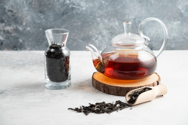 A glass teapot with dried loose teas and a wooden spoon.