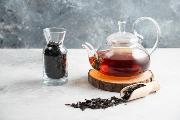 Una teiera di vetro con tè sfusi essiccati e un cucchiaio di legno.