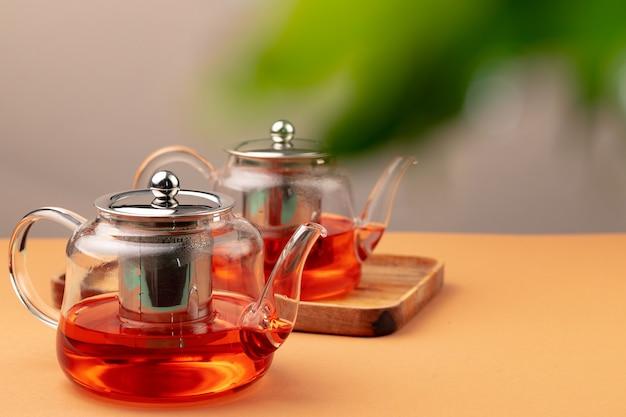 ぼやけた葉の背景に新鮮な紅茶とガラスのティーポット