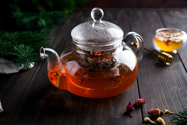 Glass teapot with freshly brewed herbal tea and honey on a wooden background.