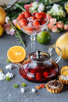Glass teapot with fruit raspberry tea and mint on a blue background with fruits and decorations.