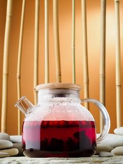 ホットレッドベリーティーカルカデとガラスのティーポット、クローズアップ。竹林と石を背景にしたお茶。繁体字中国語のお茶会のコンセプト。国際茶の日、背景。