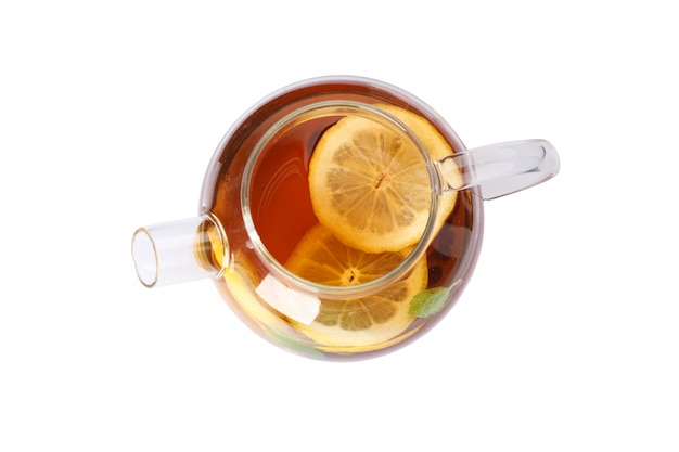 Glass teapot with lemon slices isolated on white