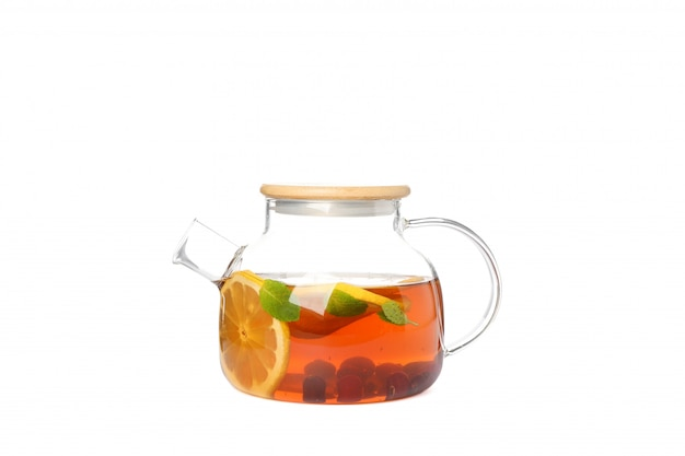 Glass teapot with lemon slices, mint and berries isolated on white