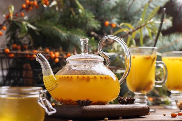オレンジ色のシーバックソーンティーとガラスのティーポット。茶色の木製テーブルに熱い冬の飲み物