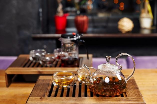 Стеклянный чайник с чаем и чашками стоит на деревянной подставке